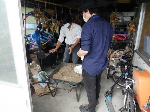 資材倉庫で検査官に説明する管理人(画像)